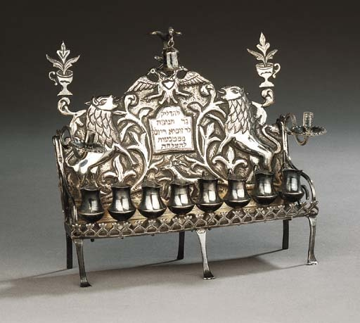 "A fine and rare silver Chanukkah lamp  Apparently unmarked probably Galicia, circa 1860  The arched rectangular backplate centred by raised shield inscribed in Hebrew: ""to kindle the Chanukkah light, belonged to Zusia Riznek [made] from 'le-Hatslacha' coins"", flanked by scrolling foliage and two rampant lions with protruding tongues, a deer below, topped by double-headed eagle, surmounted by a spread bird finial holding a bell, and flanked by two one handled vases with flowers..."