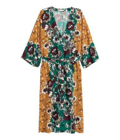 Lige skåret kjole til midt på læggen i vævet kvalitet med trykt mønster. Den har V-udskæring med skjult lukning foran. Ret lav skuldersøm og trekvartlange ærmer. Aftageligt bindebælte i taljen og høj slids i hver side. Uden for.