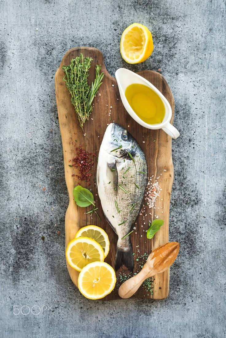 Fresh uncooked dorado or sea bream fish with lemon, herbs, oil and spices on rustic wooden board over grunge backdrop, top view
