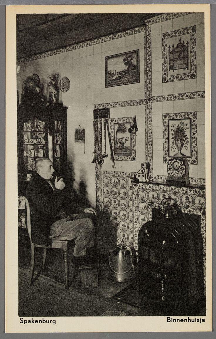 Interieur met een man zittend met voeten op een stoof, bij de kolenkachel. De schouw achter de kachel is geheel betegeld met decoratieve tegels en tegeltableaus. Naast de kachel staat een doofpot en links een buffetkast. 1930-1940 #Utrecht #Spakenburg