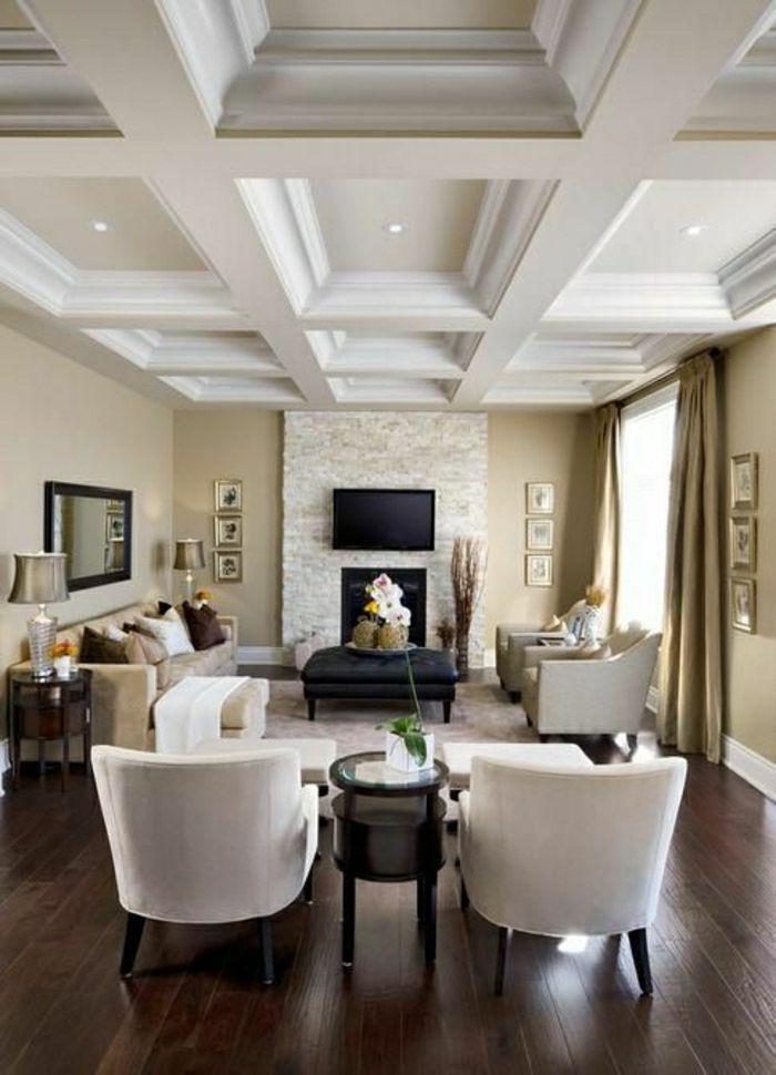 un vaste salon avec chaises taupes, sol en parquet foncé, plafond insolite avec ornement