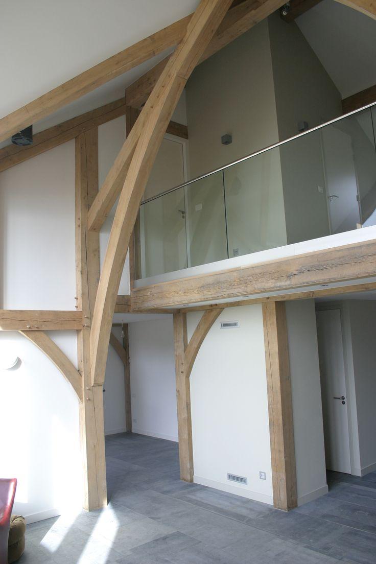 Mooi zicht op de eikenconstructie in de vide van de woonkamer. De overloop is vorozien van een hardglazen balustrade.