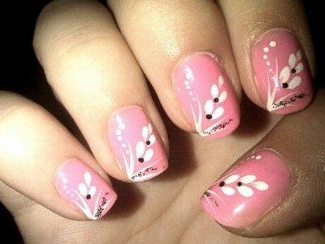 Estilos de uñas con esmalte rosa y flores de pétalos blancas con puntos negros. Son diseños de flores en uñas acrilicas