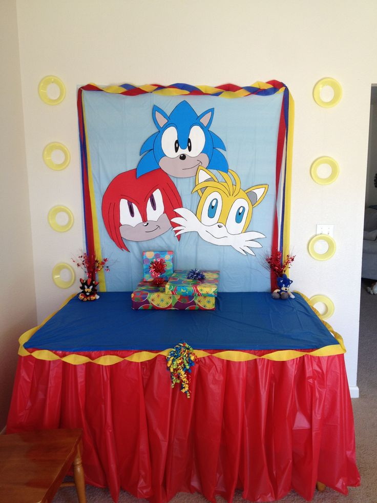 Sonic birthday party decor. Hand painted poster board character heads, yellow plastic bowls with the bottoms cut out for the rings.