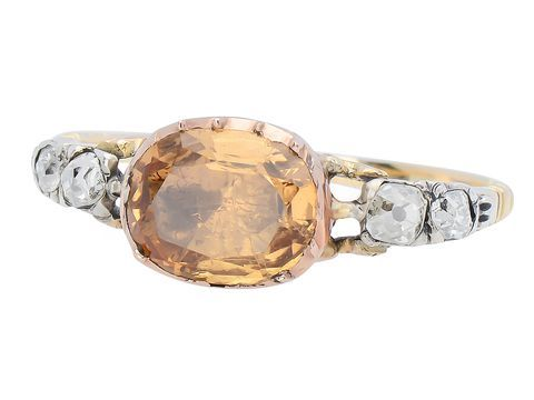 English Georgian Topaz Ring. In this ring, the center is a sunny natural topaz of 9 by 8 mm, or about 1.9 carats in weight. Its companions since the middle of the 1700's, are two old mine cut diamonds. Their total weight comes in at .30 carats and both are white to the eye, at I-J, clarity. The use of 15k rose gold displays simple linear details along with sides of the shank or band. c 1750-1770