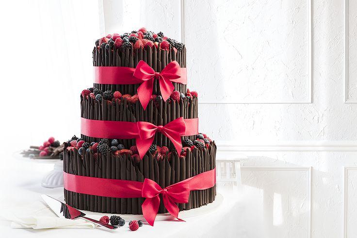 Třípatrový svatební dort s čokoládovými ruličkami, dozdobený čerstvým ovocem a saténovými stuhami.  photo: Petr Vaněk design: KANTORS CREATIVE CLUB