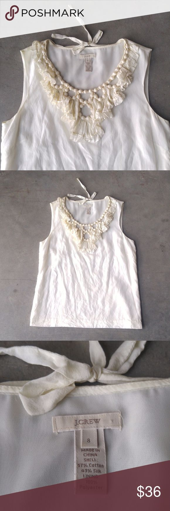 J. Crew Ivory Bead Embellished Silk Blend Tank J. Crew sleeveless blouse, size 8 (medium), in excellent condition! Color is an off-white ivory. Two flaws: small fraying on a seam in the back (7th photo) and two pen dot marks on front (8th). Both flaws are hardly noticeable. Fabric covered beads line the yoke/neckline in an intricate, cut-out design. Bow tie detail at back of neck. Size zip, full lining. Pair with a colorful pencil skirt! No trades. No modeling. Make a reasonable offer…