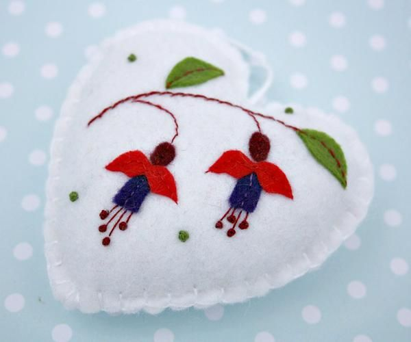 Handmade heart ornament for Christmas or any time. Red and purple fuchsia flowers hand-appliqued and embroidered on white felt. Blanket stitched edges, with a cotton loop for hanging. The back of the