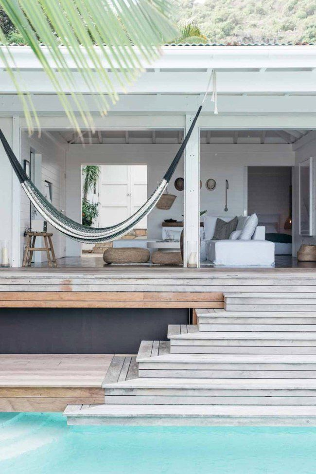 Modern beach house with gray teak deck, white painted pergola and hammock.