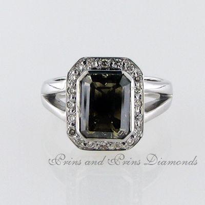 Centre stone is a 6.13ct Brown/I1 emerald cut diamond with 21 = 0.48ct round brilliant cut diamonds pavé set in a halo around the centre stone in a 9k white gold split band design