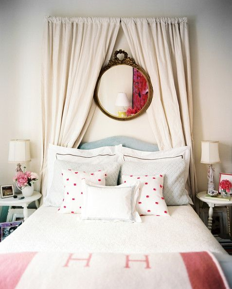 Simple curtains and a charming mirror add dramatic flair to a sweetly-dressed guest room.  Click through for more bedroom-transforming tips!