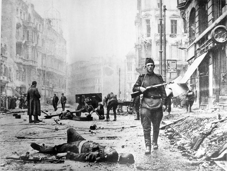A Soviet soldier stares at the cameraman as he walks past a dead SS-Untersturmführer (Second Lieutenant) on the streets of Berlín.