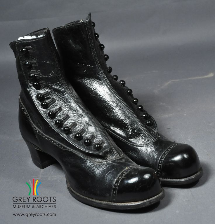 """A pair of ladies', """"Queen Alexandra Shoe"""", black, high-topped shoes from the early 20th-century. They are an ankle high boot with a patent leather toes. Grey Roots Museum & Archives Collection."""
