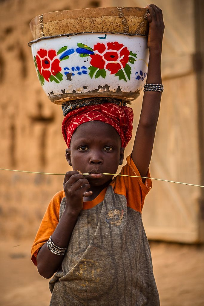Africa | Portrait of a child with a pot on her head in front of great mud mosque in Bani, in the tribal region of the Sahel, northern Burkina Faso | © Anthony Pappone
