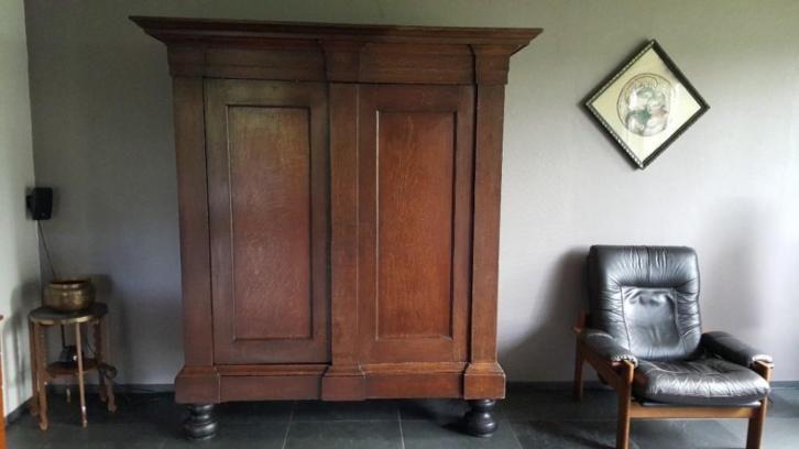 Deze antiek strakke Drentse pastoorskast van eind 1600 is in eikenhout uitgevoerd en heeft een sjieke doorleefde uitstraling. De deuren hebben gladde panelen en in de middenstijl is een geheim sleutelgat verwerkt. Helaas ontbreekt hier van de sleutel. Achter de deuren 3 planken en een lade en onder deze prachtige paneeldeuren is in de voet nog een brede verdekt opgestelde lade. Afmeting kast = bxdxh is 169 cm x 63 cm x 206 cm. Afmeting kuif 186 cm breed en 73 cm diep.