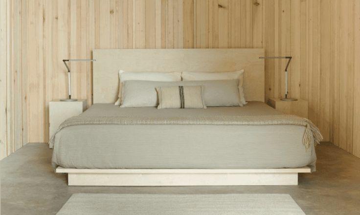 Минималистская спальня с отделкой светлым деревом. .