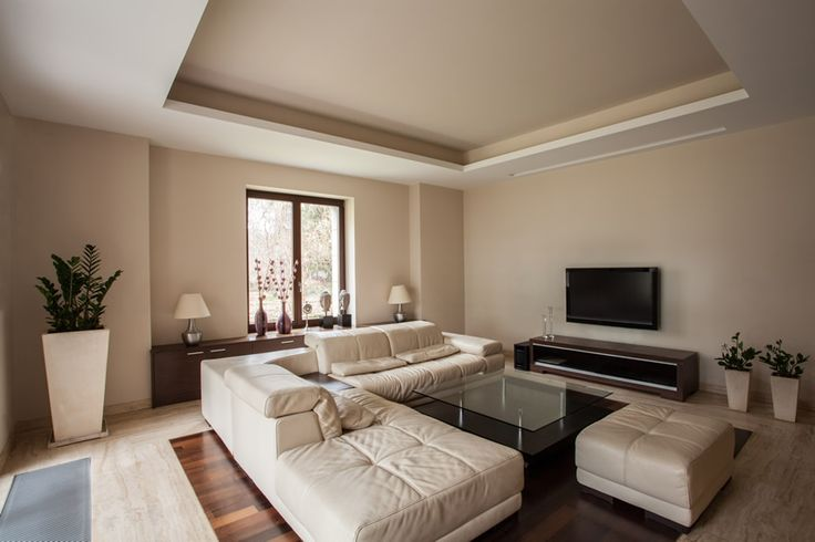 An attractive living room with large white couch with ottoman, Italian finish tiles, and dark walnut wood flooring.