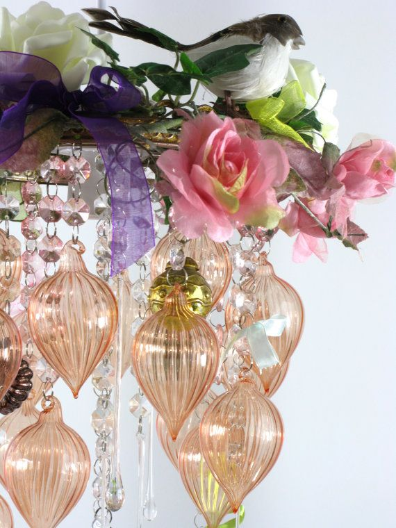 This beautiful shabby chic vintage-style chandelier is highlighted with gold glitter and decorated with birds, flowers, acrylic crystals, ribbons and glass baubles. The chandelier fits over a standard hanging bulb fitting and is suitable for use with a 60w bulb and is approx 30cm wide at its widest point and approx 40cm high measured from the uppermost piece of decoration to the longest piece of hanging decoration.  If you live in London, the chandelier will be delivered by hand personally…