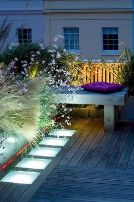 ROOF GARDEN, HOLLAND PARK, LONDON. DESIGNER: CHARLOTTE ROWE. DECKED TERRACE AT NIGHT WITH LED LIGHTING, STIPA TENUISSIMA, GAURA LINDHEIMERI WHIRLING BUTTERFLIES. Photo by Clive Nichols.