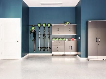 The home's well-organized garage includes a workstation, smart storage solutions and interior walls painted a deep shade of teal for an unexpected pop of color.