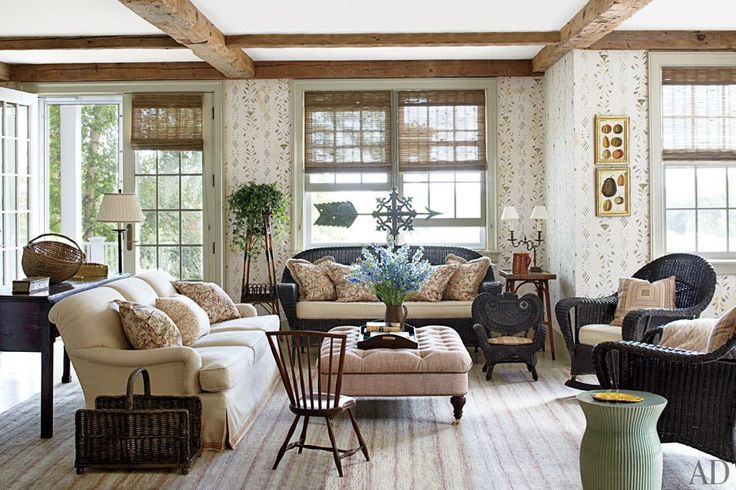 Artist Kevin Paulsen stenciled the walls of the sun-suffused family room, where a 19th-century weather vane from Cheryl A. Scott Antiques is positioned behind a wicker sofa; the ottoman is dressed in a linen by Jasper, and the carpet is by the Weaving Room.
