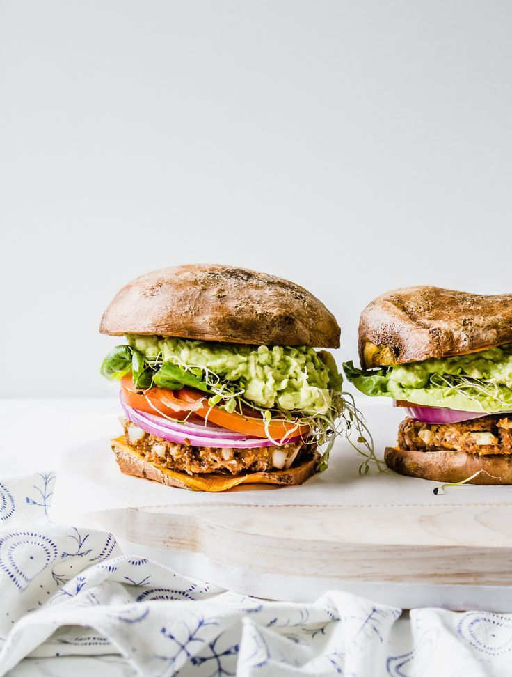 A vegan, plant-based, gluten-free burger topped with guacamole, onion, tomato, lettuce, sprouts, and BBQ sauce stuffed in a sweet potato bun!