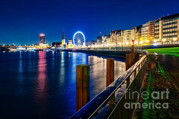 This picture shows the Riverside of the city of Dusseldorf, Germany. In the background you can see the famous Ferris wheel shining in the night.