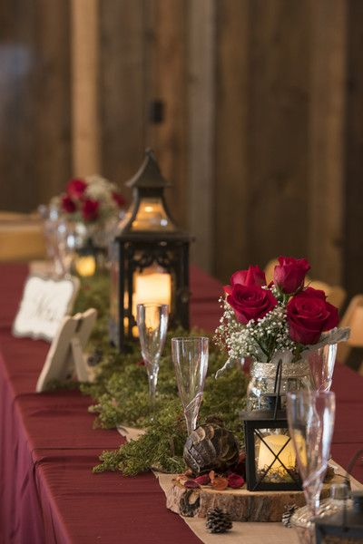 Rustic-chic burgundy centerpiece idea - wooden slices with vases filled with red roses + baby's breath with moss + vintage lanterns {Jessie Moore Photography}