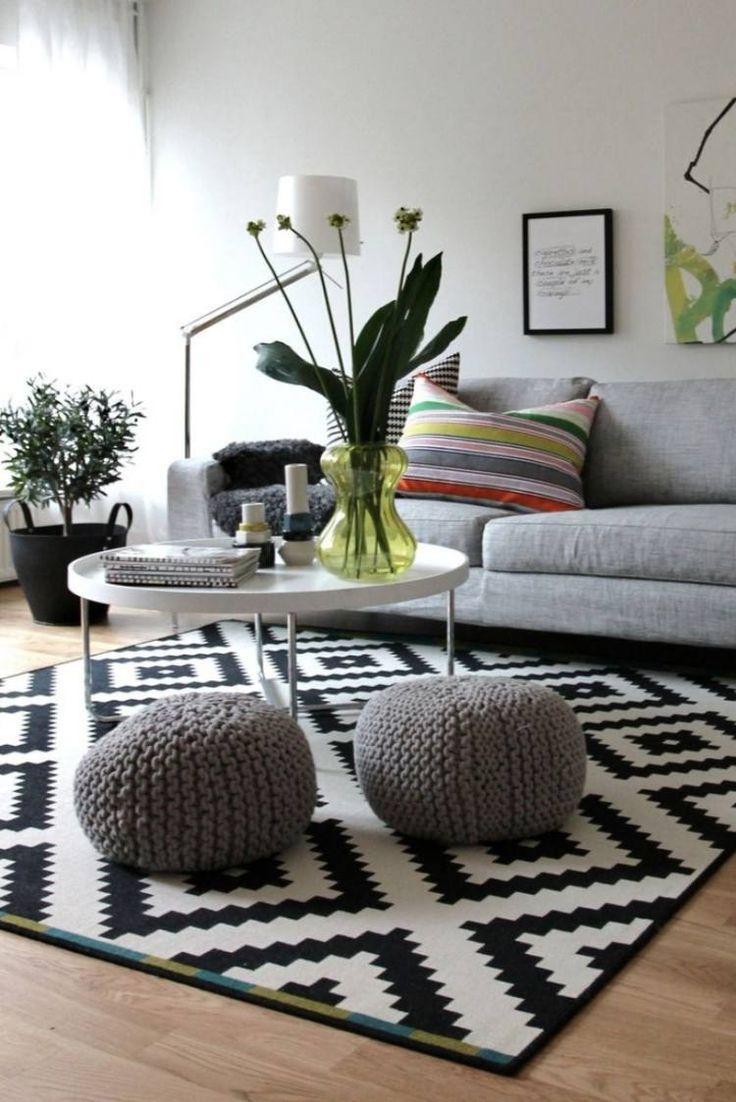 salon scandinave aménagé avec un canapé gris clair, une table basse blanche, un tapis scandinave en noir et blanc et deux poufs gris tricotés