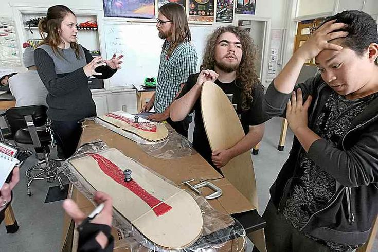 Calvin Whittaker and Hugo Fuller discuss their skateboards in the foreground as Costanoa High physical science teacher Dominic Yarbough, center, talks with USCS class aide Olivia Johnson. (Dan Coyro -- Santa Cruz Sentinel)