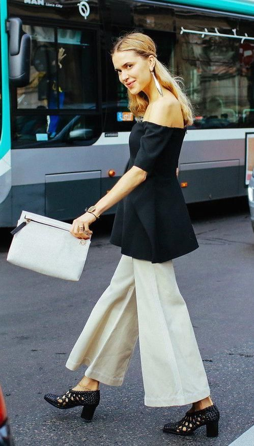 Pernille Teisbaek in a black off-the-shoulder top, beige culottes, with a Loewe bag and Repossi ring