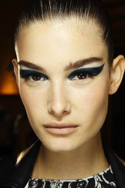 Eye-lids in a rich, metallic teal at Versace, extended from the inner corners of the eyes to the outer corners of the brows.
