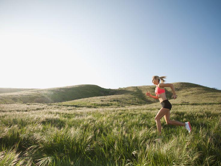 Caucasian woman running in remote field - Caucasian woman running in remote field