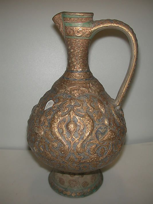 Ewer Date: 12th–13th century Geography: Iran Culture: Islamic Medium: Stonepaste; molded decoration; overglaze painted and gilded on a monochrome opaque glaze (mina'i) Dimensions: H. 11 1/8 in. (28.3 cm) Max. Diam. 6 1/4 in. (15.9 cm) Classification: Ceramics Credit Line: The Grinnell Collection, Bequest of William Milne Grinnell, 1920 Accession Number: 20.120.102