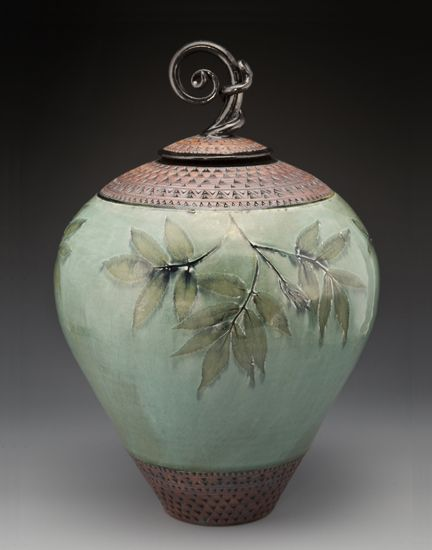 """Curlyknob Urn"" by Suzanne Crane. Flora from the Blue Ridge Mountains imprints a wheel-thrown stoneware urn with twined finial. Glazed in green, with black trim and red iron oxide on the hand-stamped border."