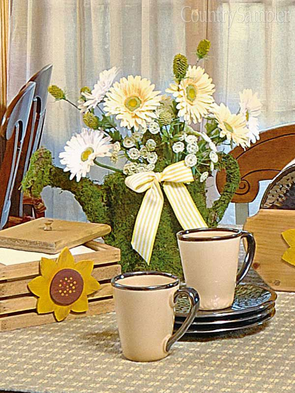 Soften the edges of a metal watering can by attaching sheet moss with spray adhesive. Arrange a bouquet of faux daisies and other florals inside, and add a matching bow for a cheerful display.