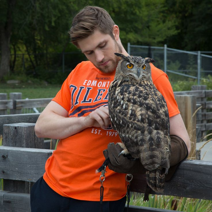 The man is holding an owl and manages to look hot doing it. How?