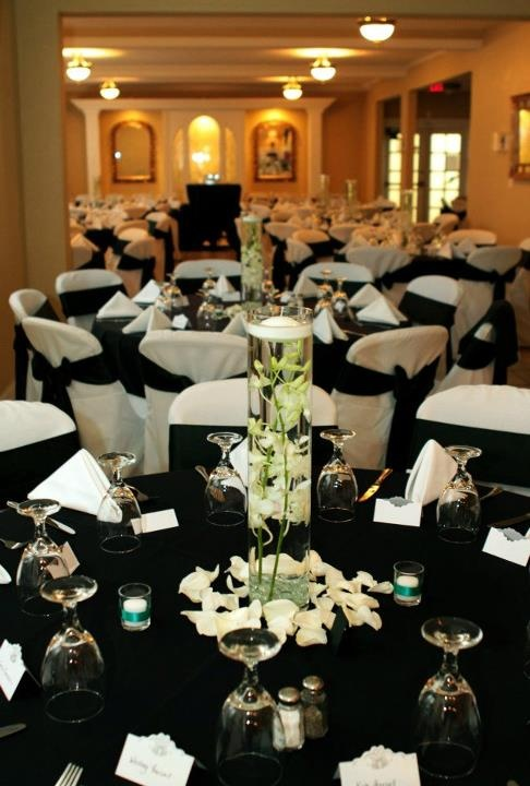Black tablecloths and white draped chairs with black bows and white linens
