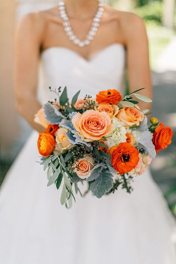 a florida bridal bouquet of loosley arranged orange ranunculus, peach roses, cream roses,white hydrangea, seeded eucalyptus and  dusty miller.