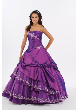 Layered Quinceañera Dress Sweet Sixteen Dress in Plum. Strapless gown with a softly curved neckline. The asymmetrical corset bodice is pleated and adorned with floral lace. The full skirt is lifted and tucked to created asymmetrical layers of tulle and taffeta.