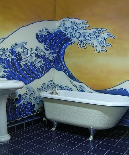A bathroom mural featuring the painting The Great Wave Off Kanagawa. Spanning a corner it is positioned as if splashing in to the bath.