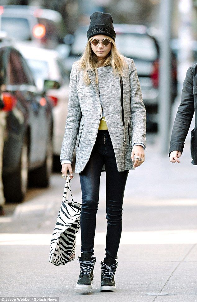 A touch of print: Cara wraps up in a coat later in the afternoon and keeps her belongings in a zebra tote