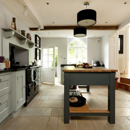 With its Aga and exposed beam, this kitchen by Lewis Alderson & Co exudes classic country charm. A freestanding island and a modern palette of grey-greens lend a contemporary touch.