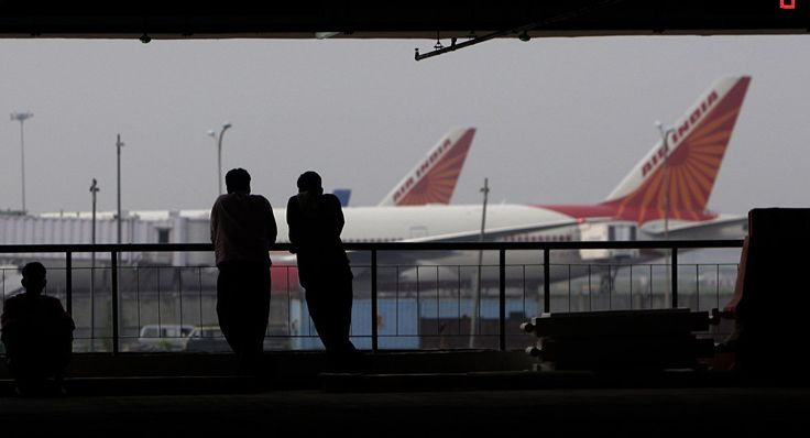 People watch aircraft from the multi-storied parking lot of the terminal 3 of the Indira Gandhi International Airport, in New Delhi, India, Thursday, July 15, 2010