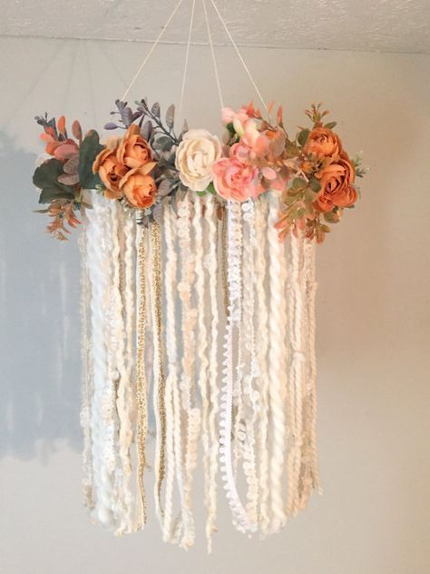 Im so in love with this mobile!! Its the first one Ive done with flowers and Im obsessed!! This dreamcatcher mobile is perfect for a baby girls nursery!! The neutral color fabrics & soft floral colors will coordinate beautifully with most décor. Boho chic with its assortment of yarns, flowers and greenery. The base is wrapped in cream ruffle yarn with a cream twine hand woven authentic web. The base is x-large size at 12 inches wide and the length is approx. 16 inches from top of flowers ...