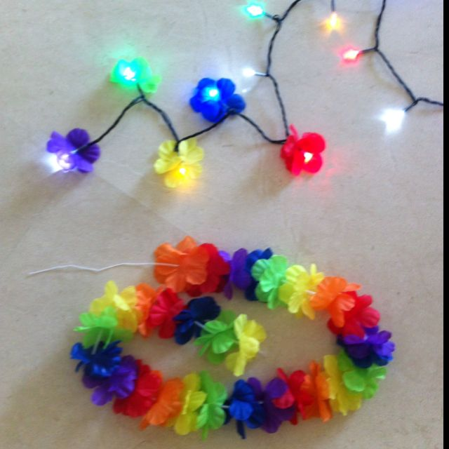 DIY luau lights: disassemble lei, cut tiny slit in center of each flower, slide 2 (or more) flowers over each bulb on string of multi-color Christmas lights (flowers can be removed before next Christmas)