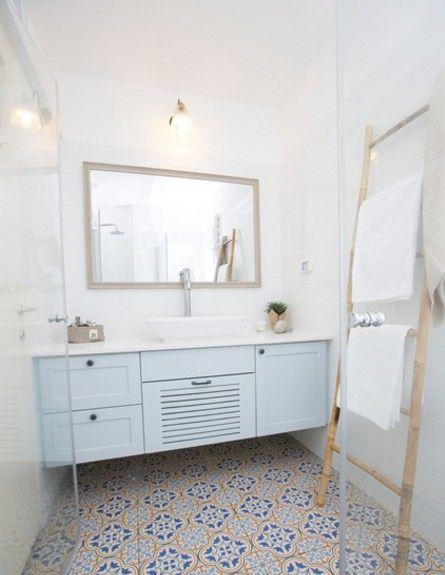 חדר הרחצה: חלל קטן יחסית שהורחב מעט על חשבון נישה לא מנוצלת שהיתה בחדר השירותים, ומצליח להכיל בתוכו ארון גדול, מקלחון מרווח ואסלה. ונשאר מקום לאמבטיית התינוק. בחרנו ארון תלוי היוצר תחושת מרחב וכן אסלות תלויות. הארון נצבע בצבע תכלת, השיש לבן ועליו כיור מונח. כחלק מנגיעות הווינטג' בחרנו ריצוף מצויר מבית HeziBank בגוון כחול ולקירות אריחי קרמיקה לבנים. מעל הארון מראה גדולה המגדילה את החלל ומעליה גוף תאורה וינטג'.