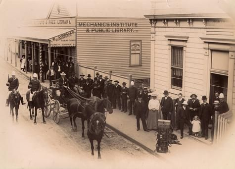 The gold escort leaving Walhalla, about 1912 Street scene includes Mechanics Institute Library, W Swingler Hairdresser, Tobacconist and Fancy Goods and the Bank of Victoria. Two mounted police are escorting a shipment of gold. Museum Victoria, Australia