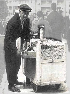 an old photo of a person selling warm peanuts and pumpkin seeds