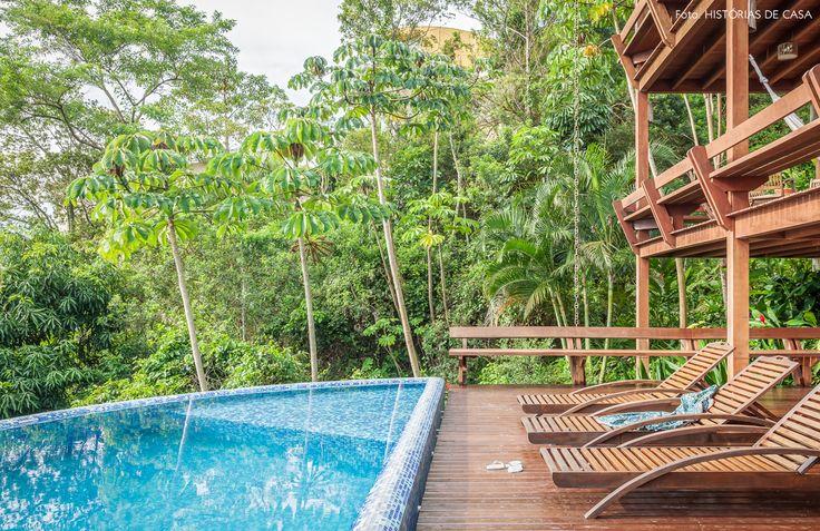 Natureza, espreguiçadeira de madeira e piscina com borda infinita.